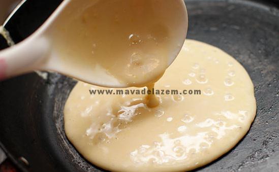 حدود 1/4 فنجان از خمیر را برداشته و روی داخل ماهی تاب داغ می ریزیم