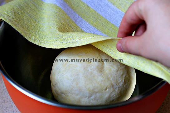 روی خمیر را با یک دستمال می پوشانیم و به مدت یک ساعت به آن استراحت می دهیم
