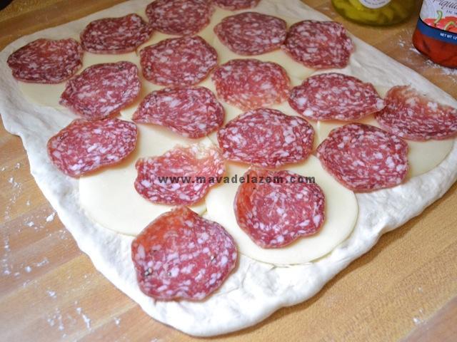 برشهای پنیر ،کالباس گوشت را روی خمیر می چینیم