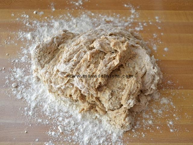 خمیر را از کاسه روی میز کار قرار می دهیم  و با بقیه آرد مخلوط می کنیم